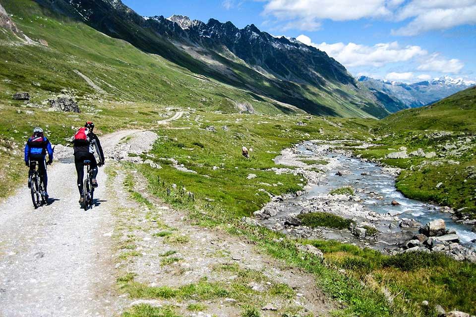 S-CAMP_deux cyclistes dans les montagnes avec une rivière