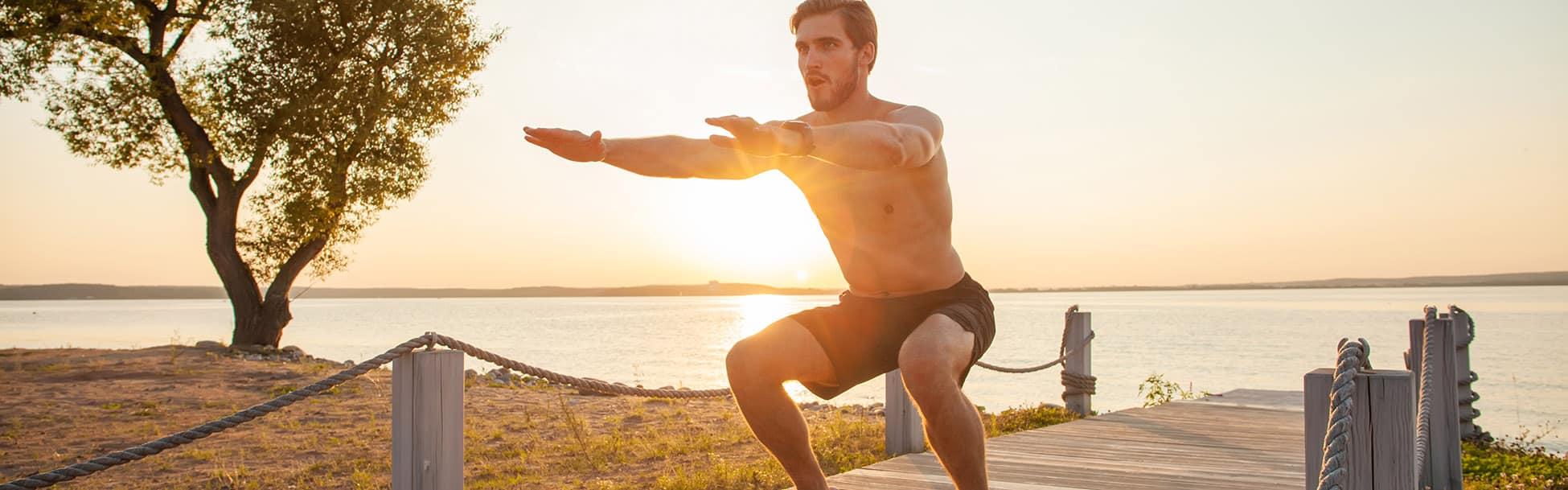 Fitness man training air squat exercise on beach outside. Fit male exercising crossfit outside. Young handsome caucasian male fitness model and instructor outdoors.