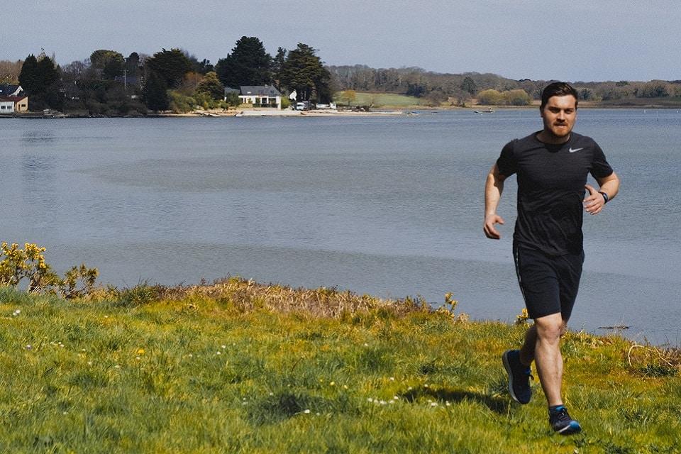 Sportif en footing au bord d'un lac vacances crossfit