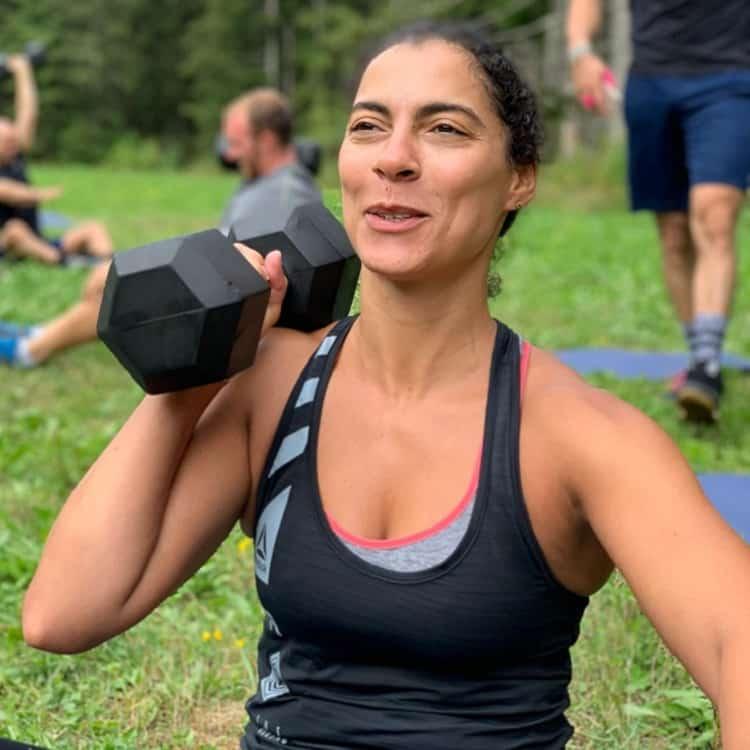 Femme de face avec Dumbell pendant les vacances sportives pour adultes