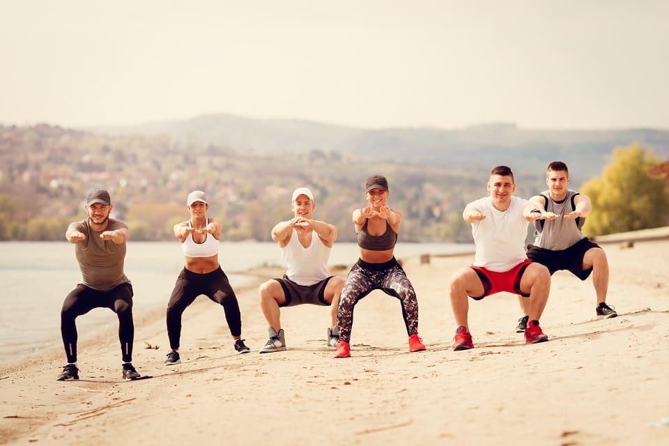 Groupe d'adultes en vacances sportives en squats sur la plage